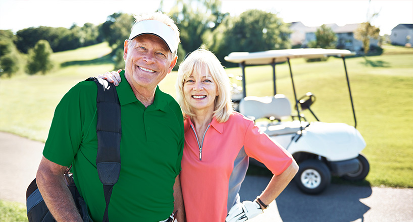 Photo of an elderly couple on a golf course.