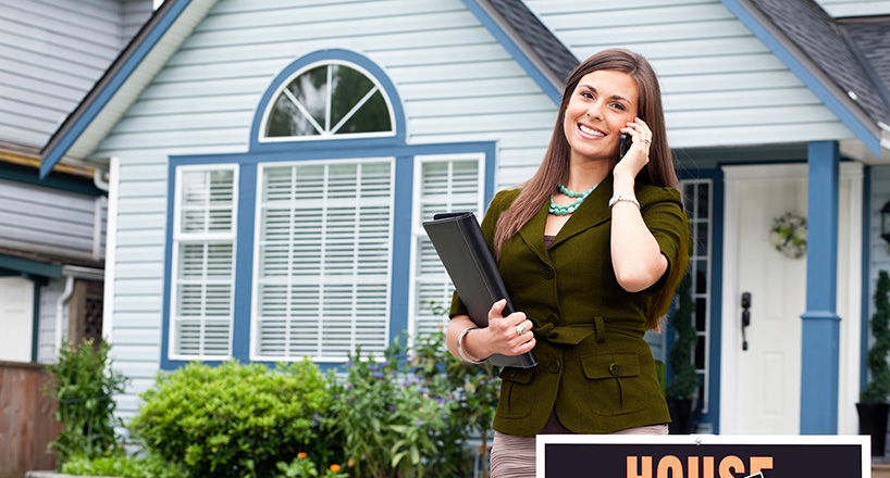 Photo of real estate agent in front of a recently sold house.