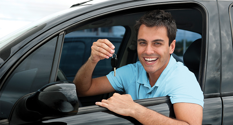 Photo of a happy man in his car that he purchased with a Mission Fed Autoland auto loan