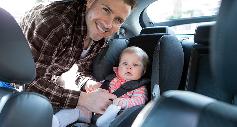 Photo of smiling dad securing his baby in a car safety seat.