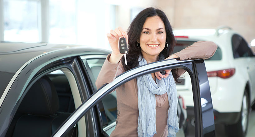 Photo of a smiling woman holding the keys to her new car