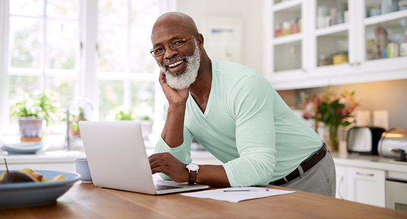 Photo of man with his laptop on his kitchen table using budgeting tools online.