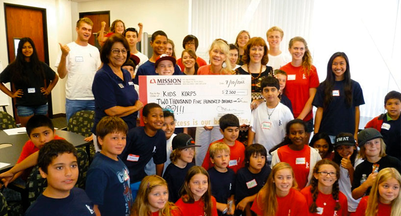 Photo of student and teachers with giant check.
