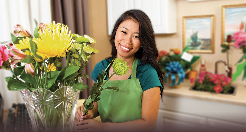 woman with flowers happy after opening a credit union checking account