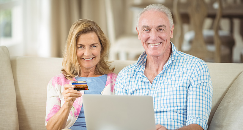 Photo of a couple checking their credit score on their laptop.