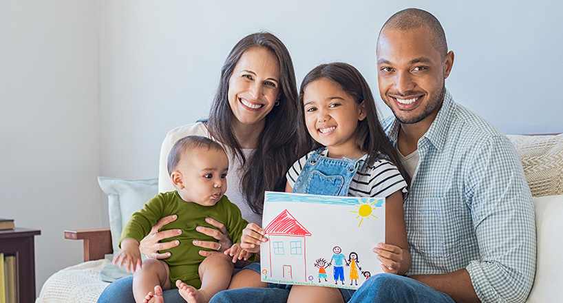 Photo of a husband and wife with their daughter and baby boy holding their kid's drawing of their family's new house purchased with Mission Fed Home Loan.