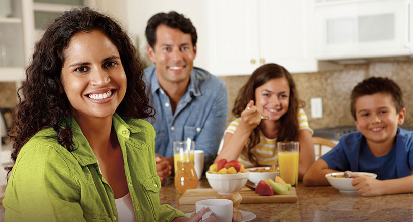 Photo of happy family at kitchen table.