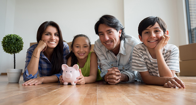 Photo of a family with a piggy bank who will purcahse their new home with a Mission Fed Home Loan.