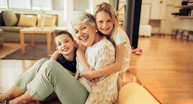 Photo of a grandmother with her two grandchildren in her new home purchased with a Mission Fed Home Loan.