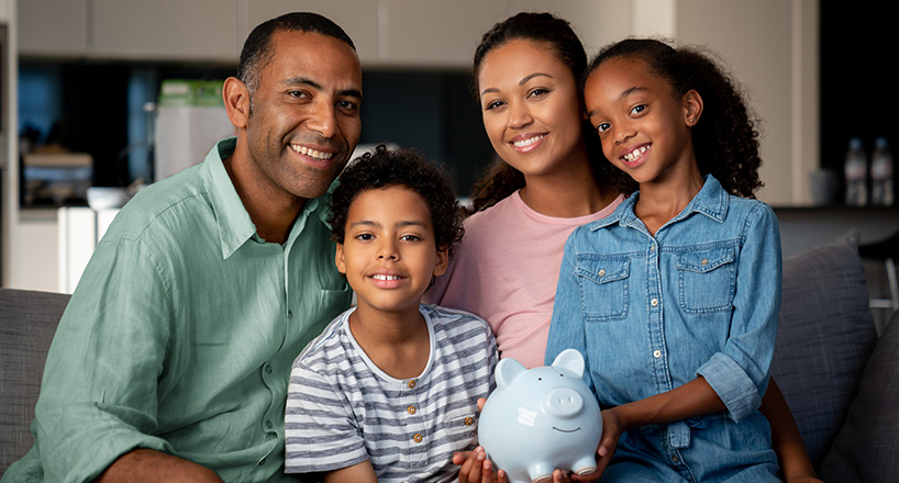 Photo of a family with a piggy banks who are saving for purchases, emergencies, college and retirement simultaneously.
