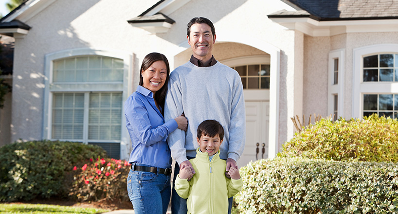 Photo of a husband and wife and their son in front of their new home purchased with a Mission Fed Home Loan.