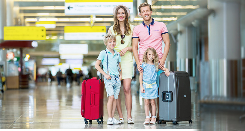 Photo of a family at an airport ready for their flight they paid for with Mission Fed Skip-A-Pay.