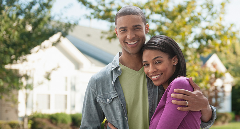 Photo of a couple in front of their new home purchased with a Mission Fed Home Loan.