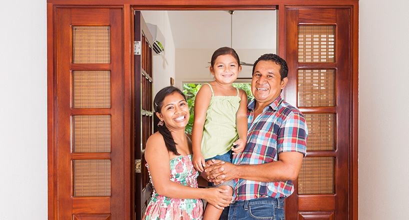 Photo of a husband and wife holding their daughter in their new home purchased with a Mission Fed Home Loan.