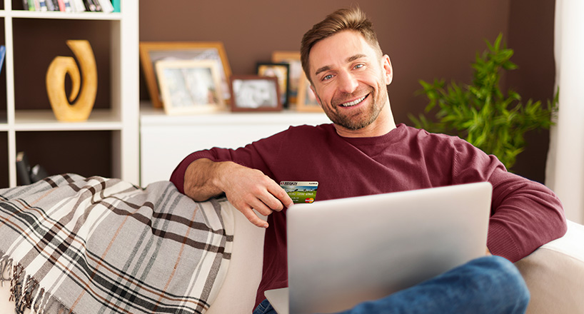 Photo of a man checking his credit score on his laptop.
