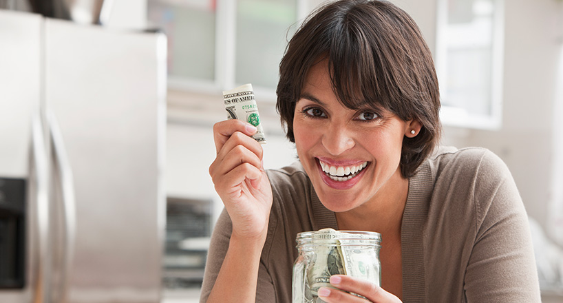 Photo of a woman in her kitchen saving cash in a mason jar.