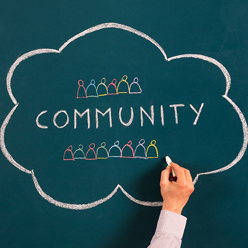 Photo of the concept of community being drawn on a chalkboard.