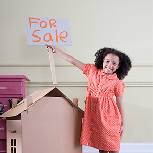 photo of a girl holding a for sale sign over a cardboard house