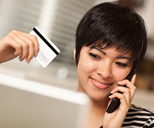 Woman on the phone reviewing her credit card benefits.