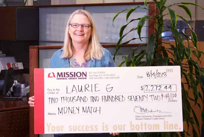 Photo of Laurie G. holding her Money Match check