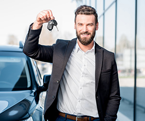 Man holding the keys to his new SUV.