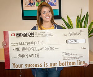 Photo of Alexandria E., a recent Mission Fed Money Match winner, holding up her giant check.