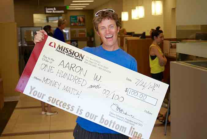 Photo of Aaron W. with giant check