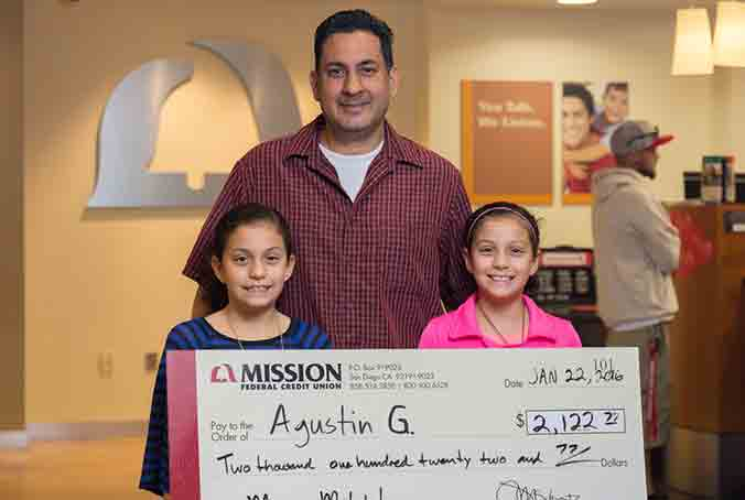 Agustin G. and his daughters with giant check