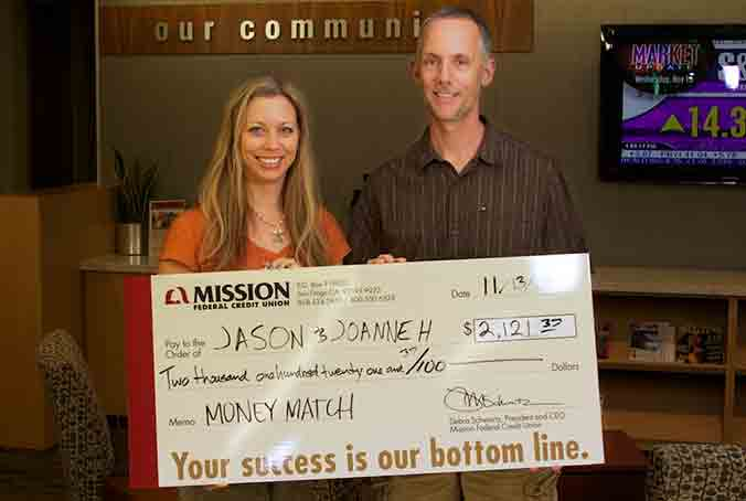 Photo of Joanne and Jason H. holding their July Home Loan Payment check with her husband