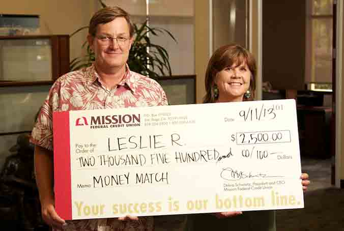 Photo of Leslie R. holding her July Home Loan Payment check with her husband