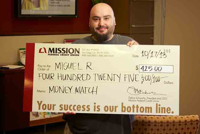 Photo of Miguel R. holding his Money Match check