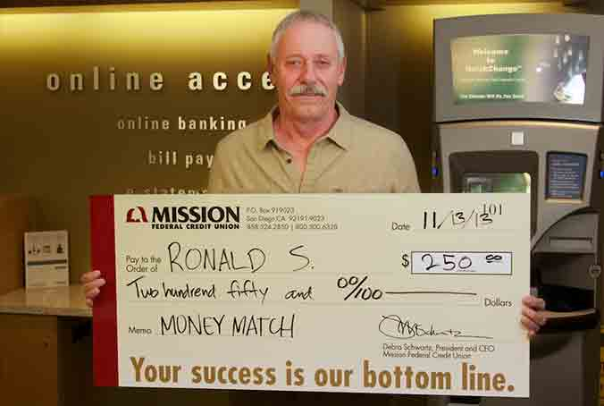 Photo of Ronald S. holding his Money Match check