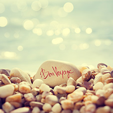 photo of rocks on a beach and the words bon voyage written on a large rock