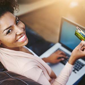 Photo of a woman managing her finances online and holding her Mission Fed Platinum Credit Card.