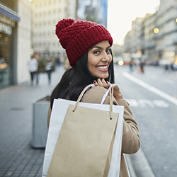 Photo of a smiling woman with shopping bags slung over her shoulder.