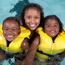 Photo of happy mom with her kids in a swimming pool.