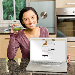 Photo of a smiling young woman with a Mission Fed credit card using her laptop for online banking.