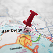 Photo of pushpin marking San Diego on a map.