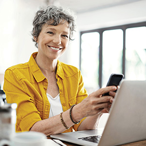 Photo of a smiling woman using her phone for Mission Fed Online Banking.