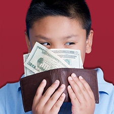 Photo of a boy holding a wallet full of money.
