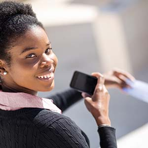 Photo of a happy Mission Fed member using her checking account with Mobile Banking.