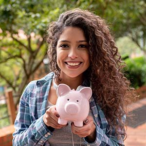 Young adult with piggy bank