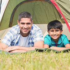 photo of a father and son in a camping tent