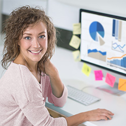 Photo of smiling woman using her desktop to manager her Mission Fed accounts.