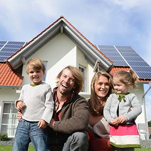 Couple with little kids in front of solar panel home.