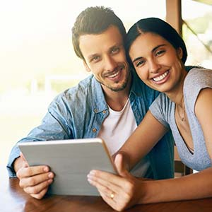 Photo of a happy couple viewing Mission Fed's services online.