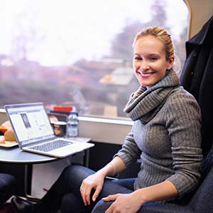 Photo of a woman traveling on a train in Germany on vacation and checking her laptop.