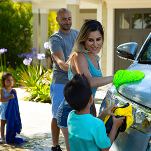 Family washing their car that was refinanced with a Mission Fed auto loan.