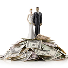 Photo of a figure of a bride and groom standing on a pile of money.