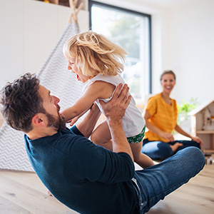 Father and mother playing with their daughter in their new home.